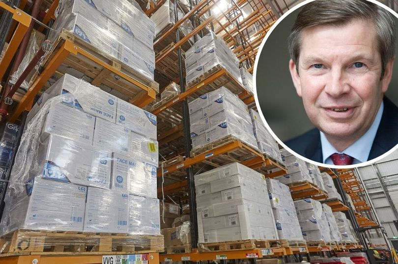 Arco managing director David Evison and the pallets of face masks ready for distribution